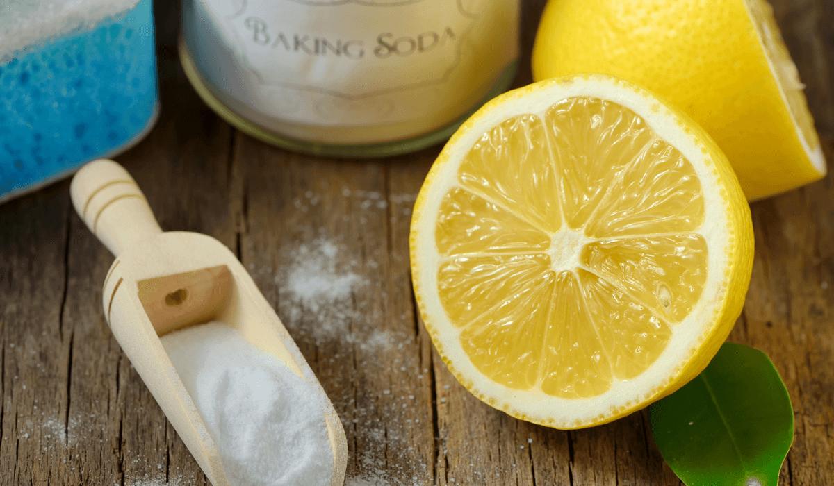a scoop of baking soda beside a lemon cut in half