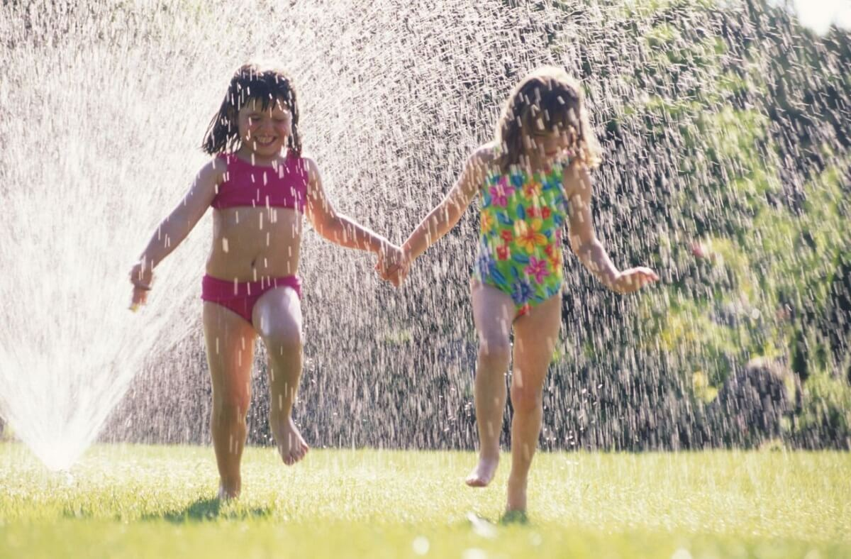 Kids running through sprinkler